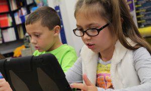 Zwei Kinder lernen am Rechner